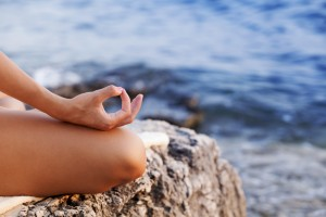 Woman doing yoga at sunset, lotus position, copy space
